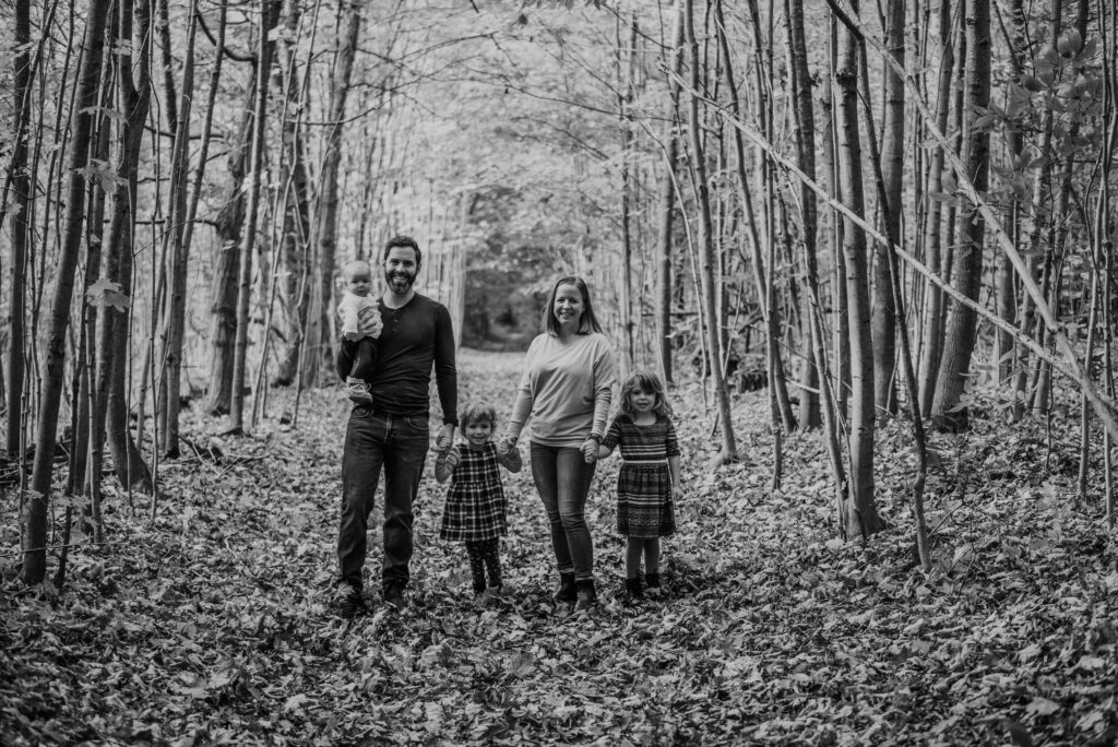 Family with parents and three kids walking together down a forest trail in the fall